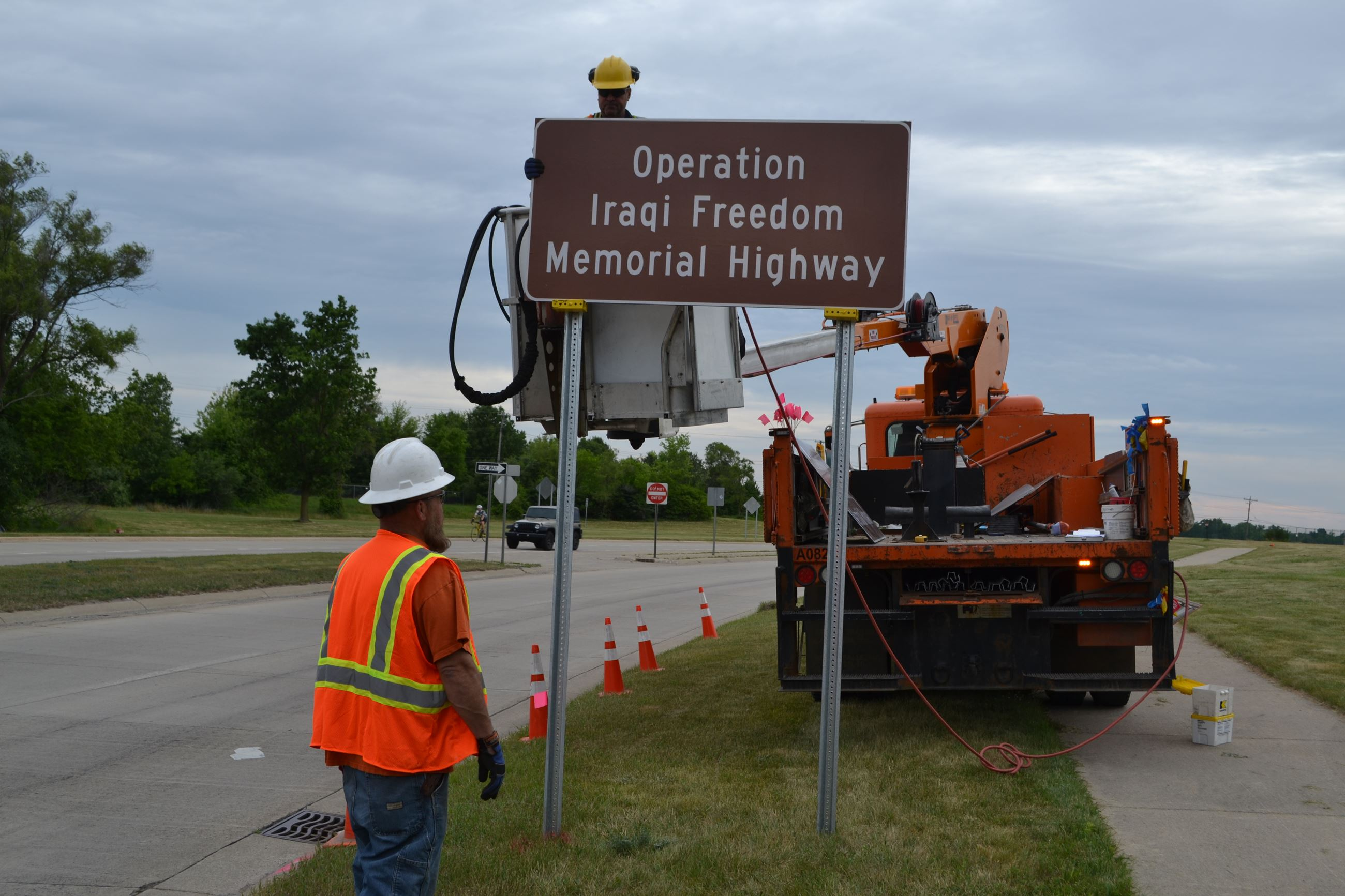 RCOC employees install Operation Iraqi Freedom Memorial Hwy sign on Williams Lake Road north of M-59