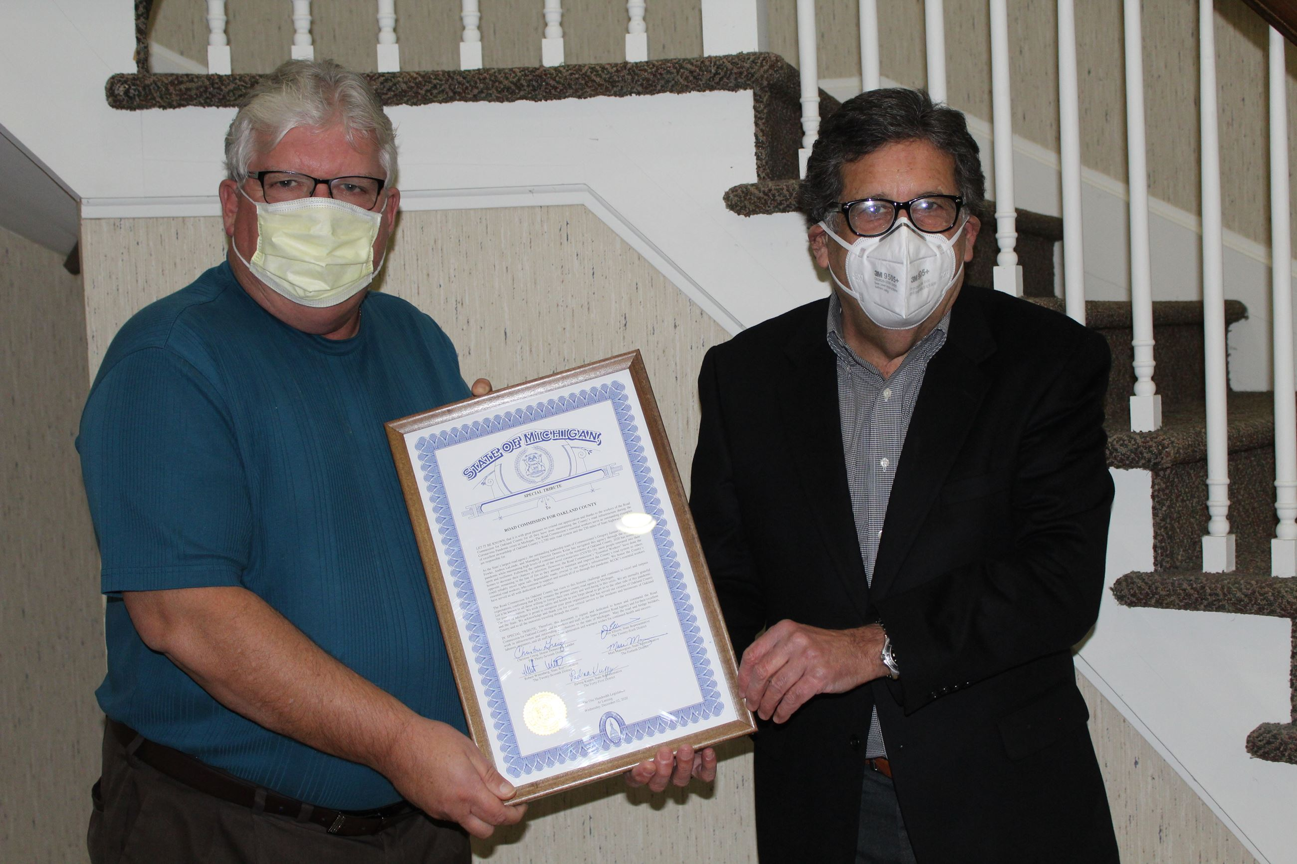 Greg Jamian (right) and Dennis Kolar display state tribute recognizing R.C.O.C. workers during pande